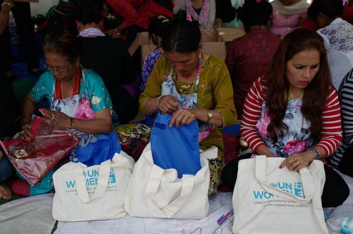 Nepalilaisten naisjärjestöjen aktivistit pakkaavat UN Womenin toimittamia vaatteita ja hygieniatarvikkeita jaettavaksi kaikkein heikoimmassa asemassa oleville naisille.
