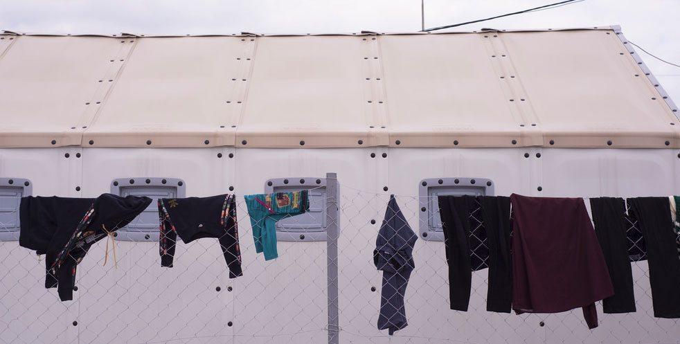 Naiset ripustivat pyykkiä kuivumaan vapun alla Tabanovcen vastaanottokeskuksessa. (Kuva: UN Women/Mirjana Nedeva)